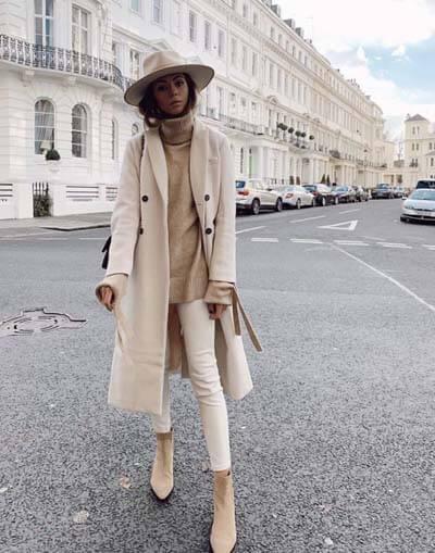 Tenue couleurs neutres : manteau écru, pull beige, skinny écru, boots beiges